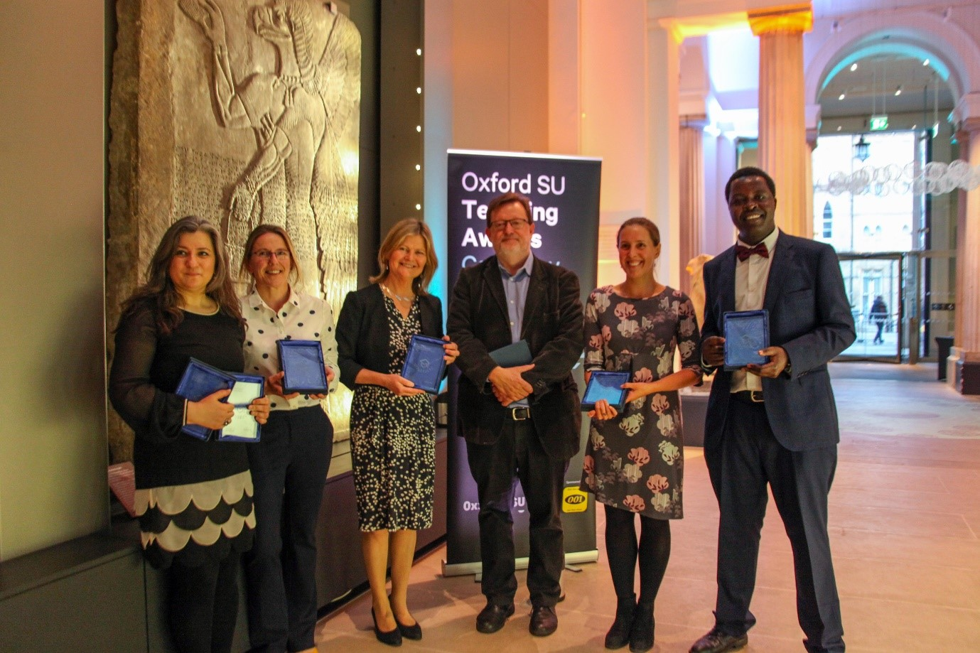 Winners of the Oxford Students' Union Annual Teaching Awards 2019 holding their awards in the Ashmolean foyer in front of a teaching awards banner